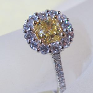 18 KT White Gold Ring Featuring a .70 CT Center Yellow Diamond and .42 CT tw White Diamonds